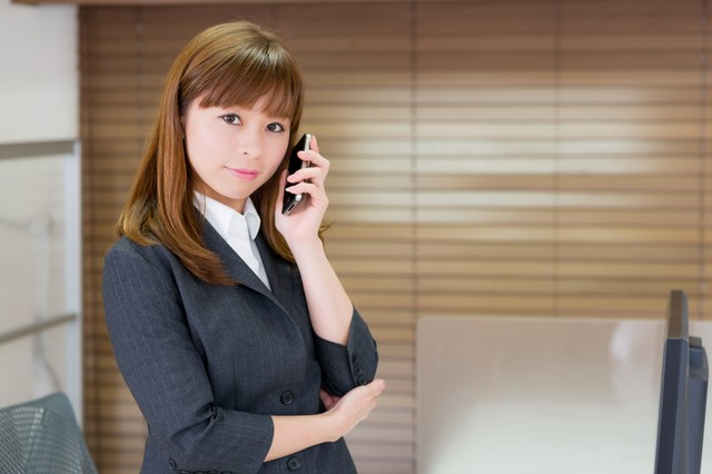 オフィスで電話するOLの写真
