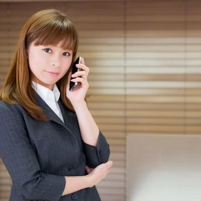 「オフィスで電話するOL」の写真素材