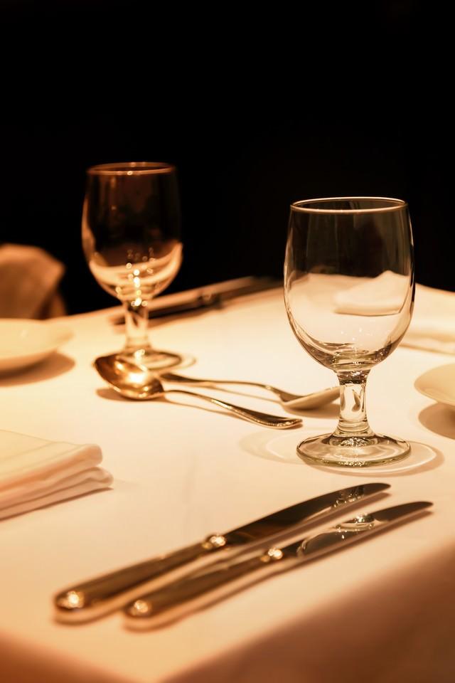 テーブルにおかれた銀のナイフとグラスの写真