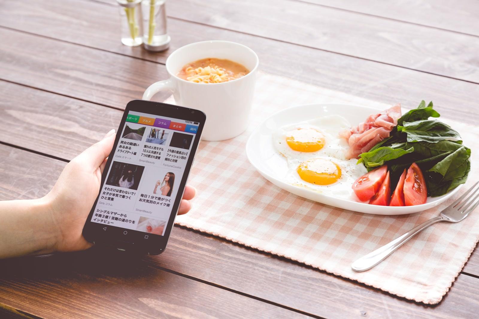 「朝食を食べながらニュースアプリをチェック」の写真