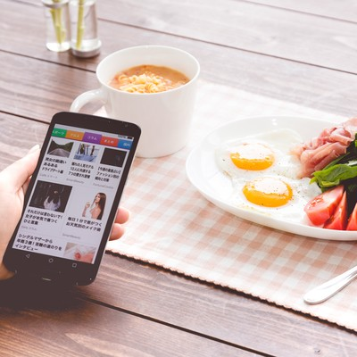 「朝食を食べながらニュースアプリをチェック」の写真素材