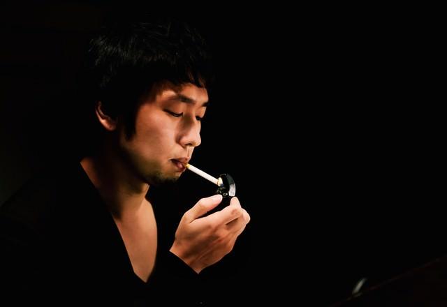 暗いBARでタバコに火をつける男性の写真