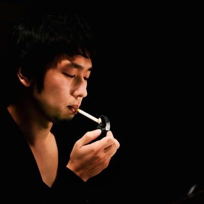 「暗いBARでタバコに火をつける男性」の写真素材