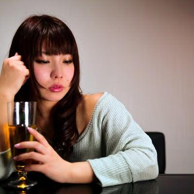 「飲みすぎて赤くなる女性」の写真素材