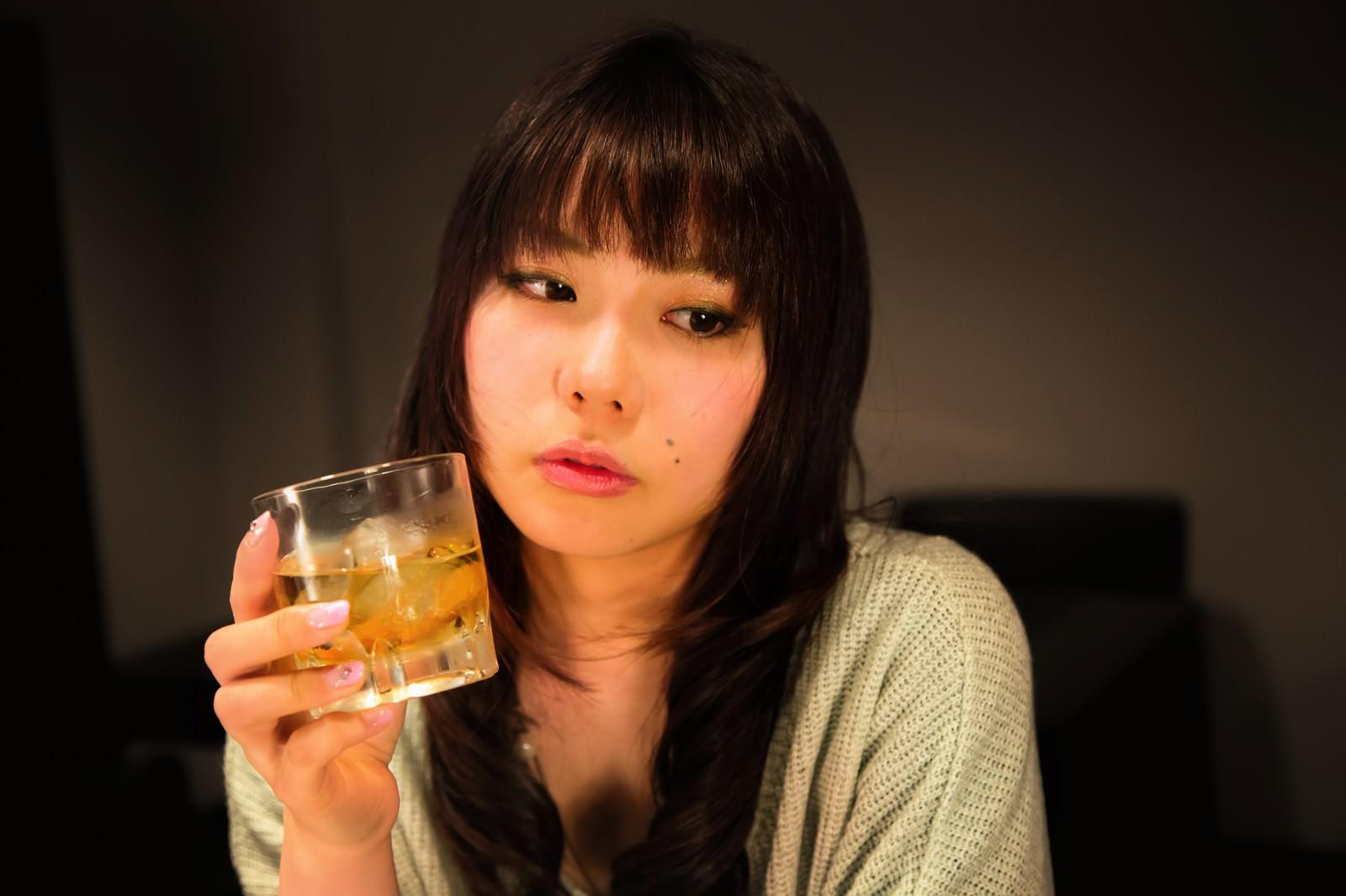 「「最近疲れちゃったなー」とお酒を飲む女性」の写真[モデル:Lala]