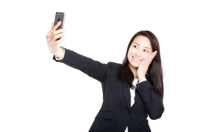 自撮りで歯痛ポーズを決める女性社員の写真