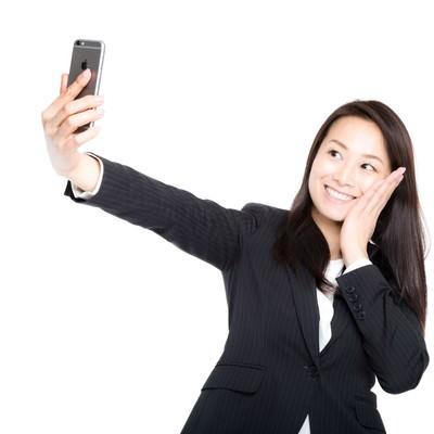 「自撮りで歯痛ポーズを決める女性社員」の写真素材