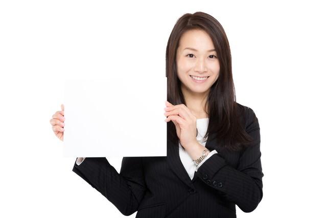 テロップを掲げる受付の女性の写真