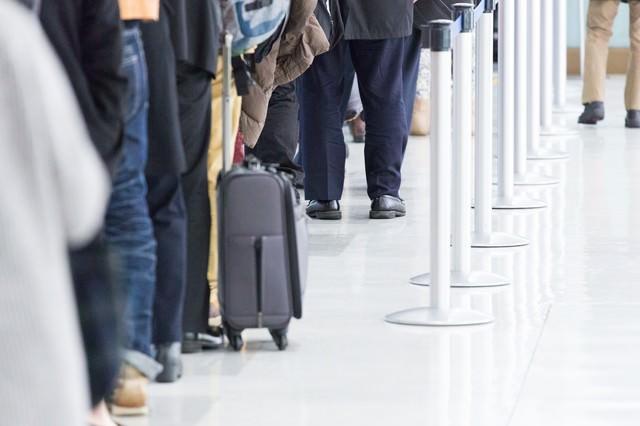 空港の入場ゲートに並ぶ人々