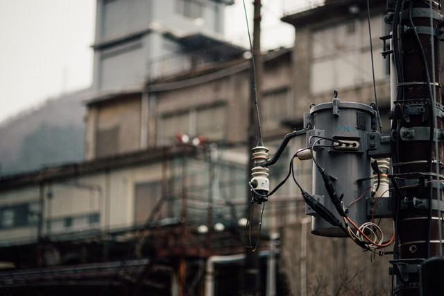 小雨が降る廃墟と電柱の写真