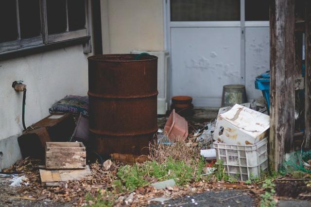 錆びたドラム缶とゴミの写真