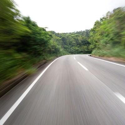 スピード感のある道路(森)の写真