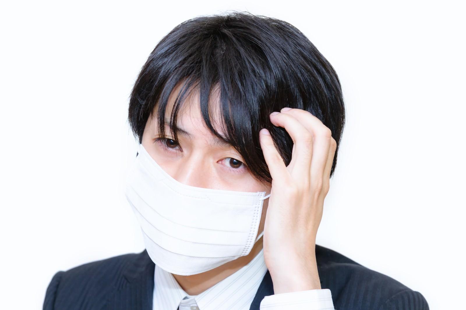 「風邪をひいたかもしれないマスクをした男性」の写真[モデル:Tsuyoshi.]