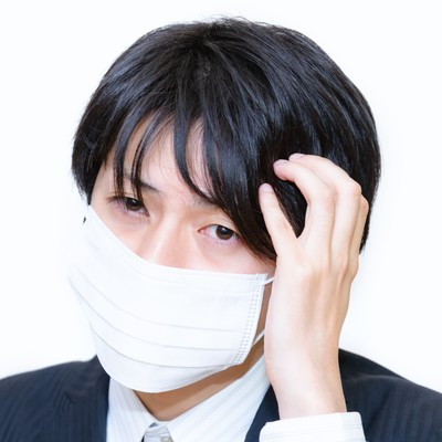 「風邪をひいたかもしれないマスクをした男性」の写真素材