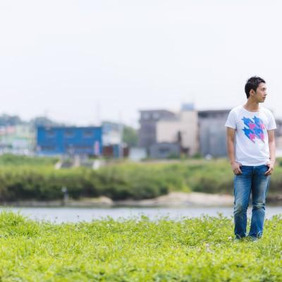 「河川敷を歩く男性」の写真素材