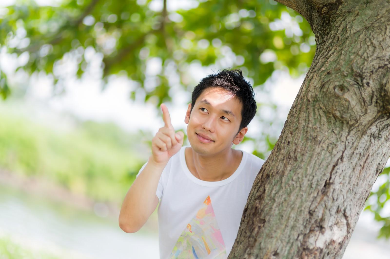 「木の陰からひょっこと現れて指をさす男性」の写真[モデル:大川竜弥]