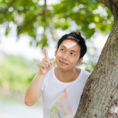 「木の陰からひょっこと現れて指をさす男性」の写真素材