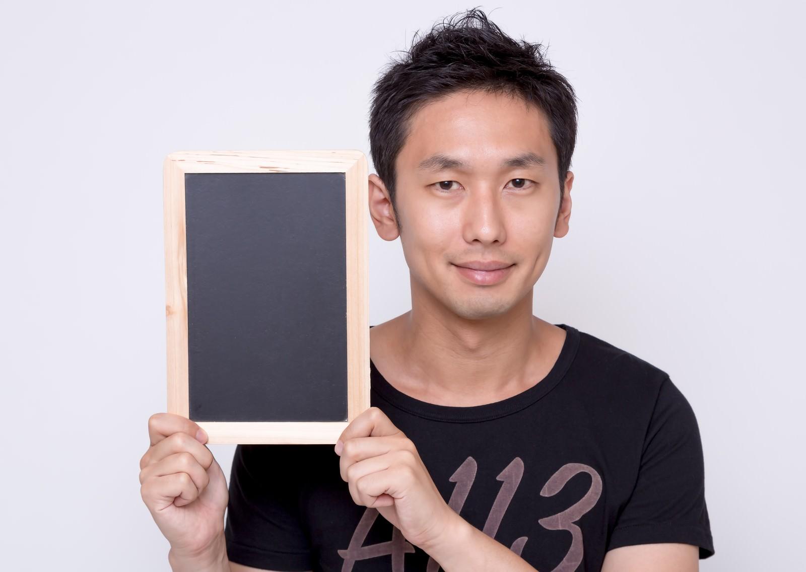 「小さい案内板を見せる男性」の写真[モデル:大川竜弥]