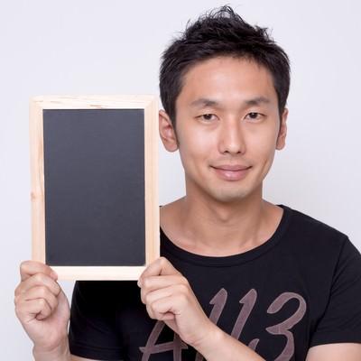 「小さい案内板を見せる男性」の写真素材