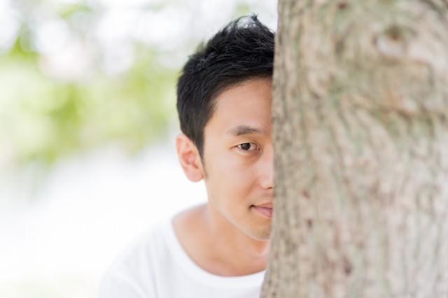 木陰に隠れてこちらを見る男性の写真
