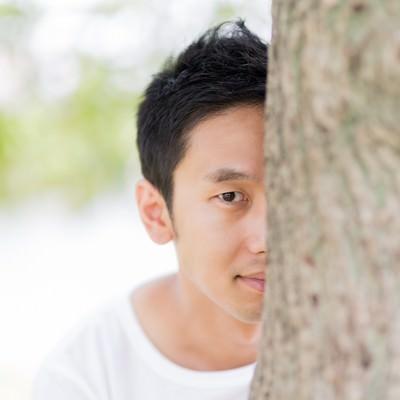 「木陰に隠れてこちらを見る男性」の写真素材