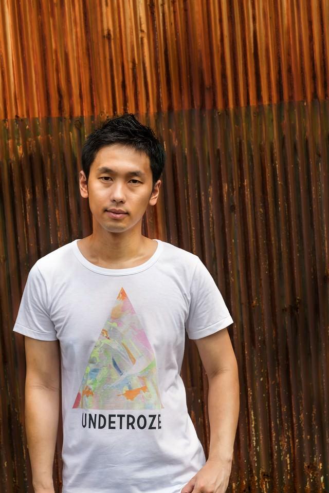 廃工場とオシャレなTシャツを着た男性の写真