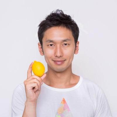 「雑誌の表紙でレモンを持つ男性」の写真素材