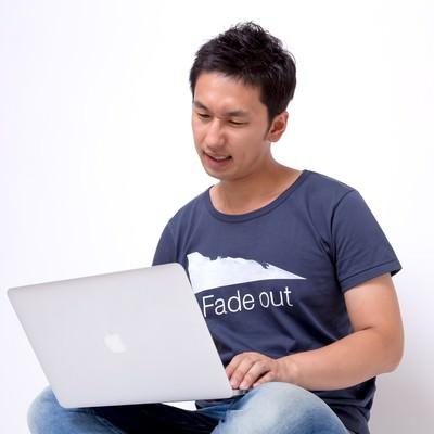 「PCを触り苦い顔をするフリーランスの男性」の写真素材