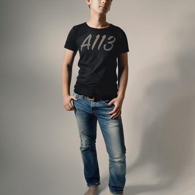 「A113と書かれたTシャツを着てポージングする男性」の写真素材