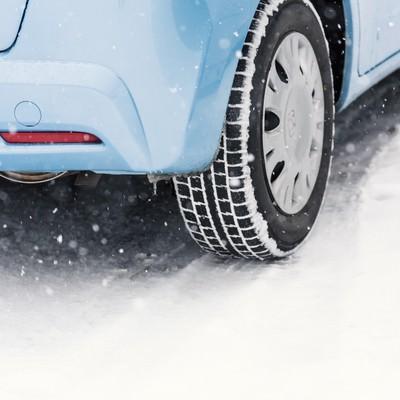 「雪道と車のスタッドレスタイヤ」の写真素材