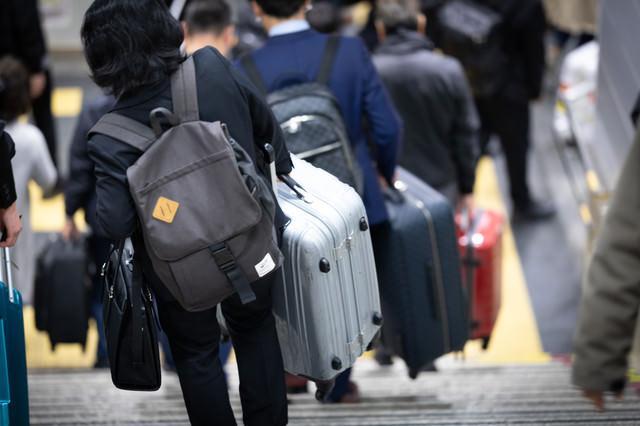 重たいスーツケースを持って階段を下りるトラベラーの写真