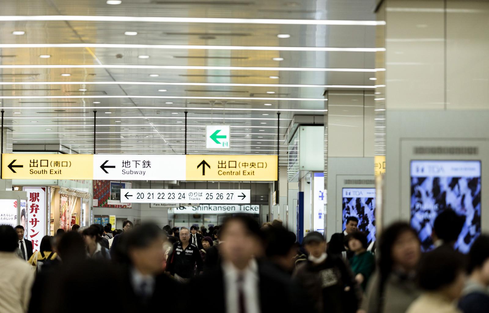 「新幹線乗り場の人混みと案内板」の写真