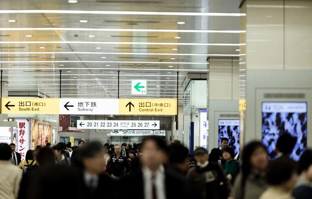 新幹線乗り場の人混みと案内板の写真