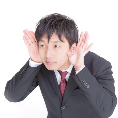 「「なになに?もう一回言って」っと両耳に手を当てるビジネスマン」の写真素材