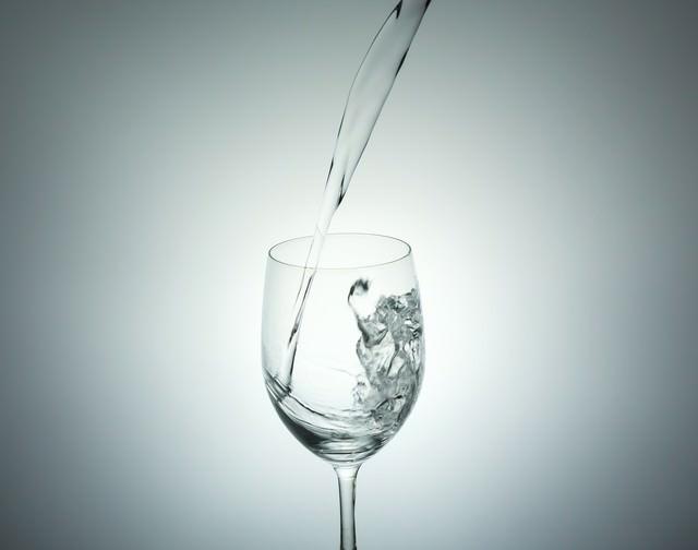 ミネラルウォーターをグラスに注ぐの写真