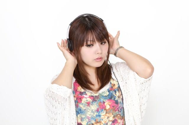 ヘッドフォンで音楽を聴く女性の写真