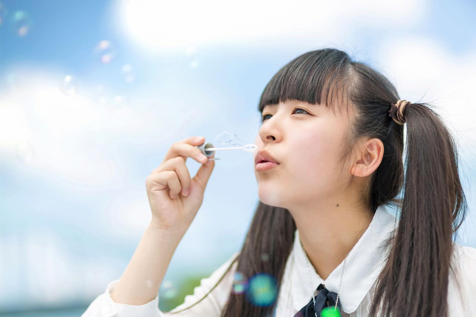 「空に向かってシャボン玉を吹くツインテールの女の子」の写真[モデル:こころ]
