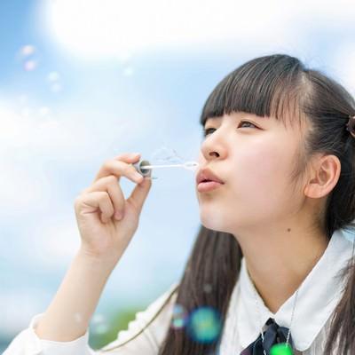 「空に向かってシャボン玉を吹くツインテールの女の子」の写真素材