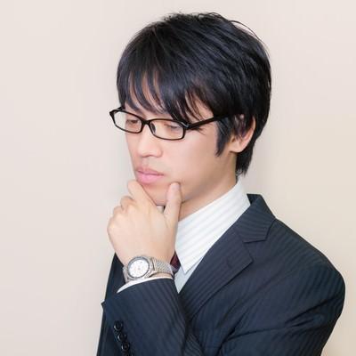 「スーツ姿の考える男性」の写真素材
