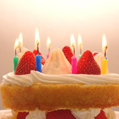 「ケーキのロウソクに火をつけて「おめでとう」」の写真素材