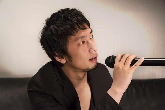 カラオケを歌うホスト風の男性の写真