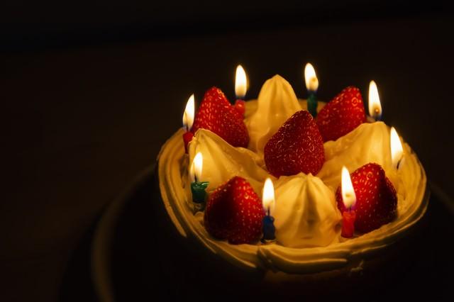 ロウソクの明かりとイチゴのケーキの写真