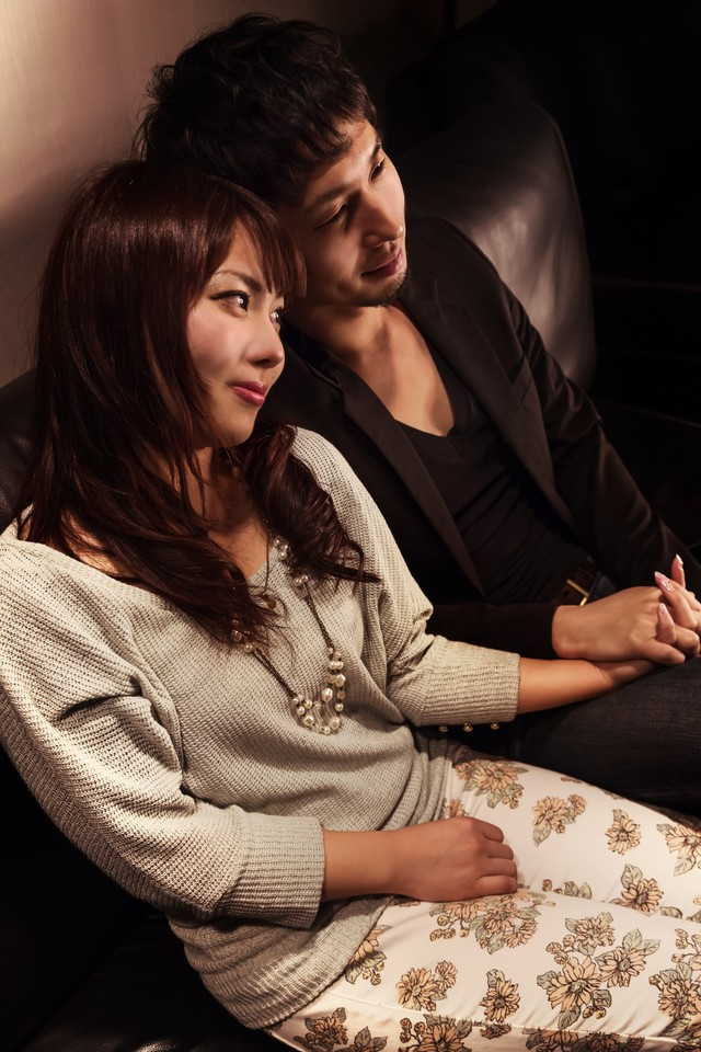 ソファーの上で手を握り合う男女の写真