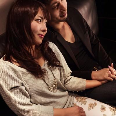 「ソファーの上で手を握り合う男女」の写真素材
