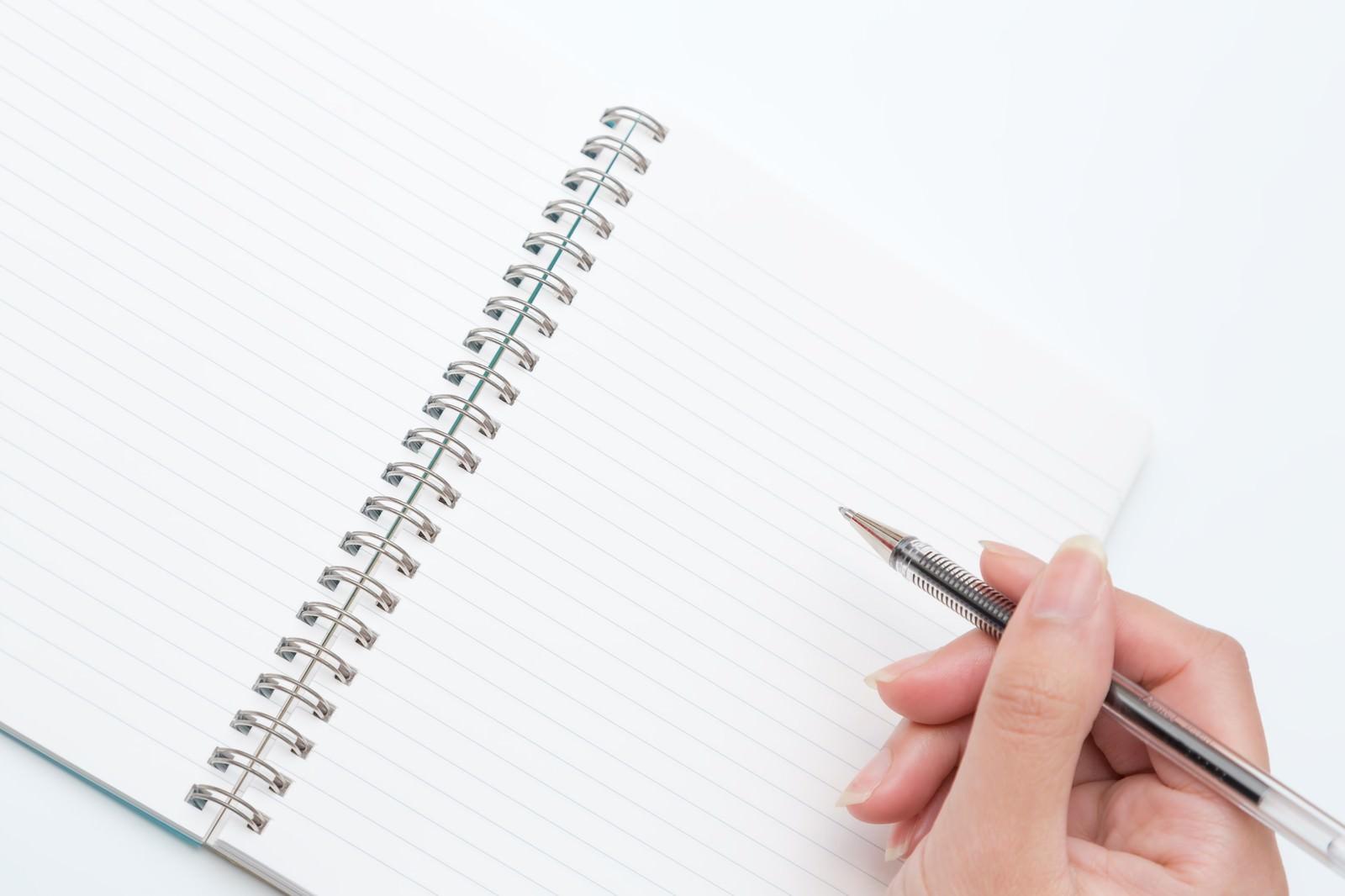 「ペンを持つ手とノート」