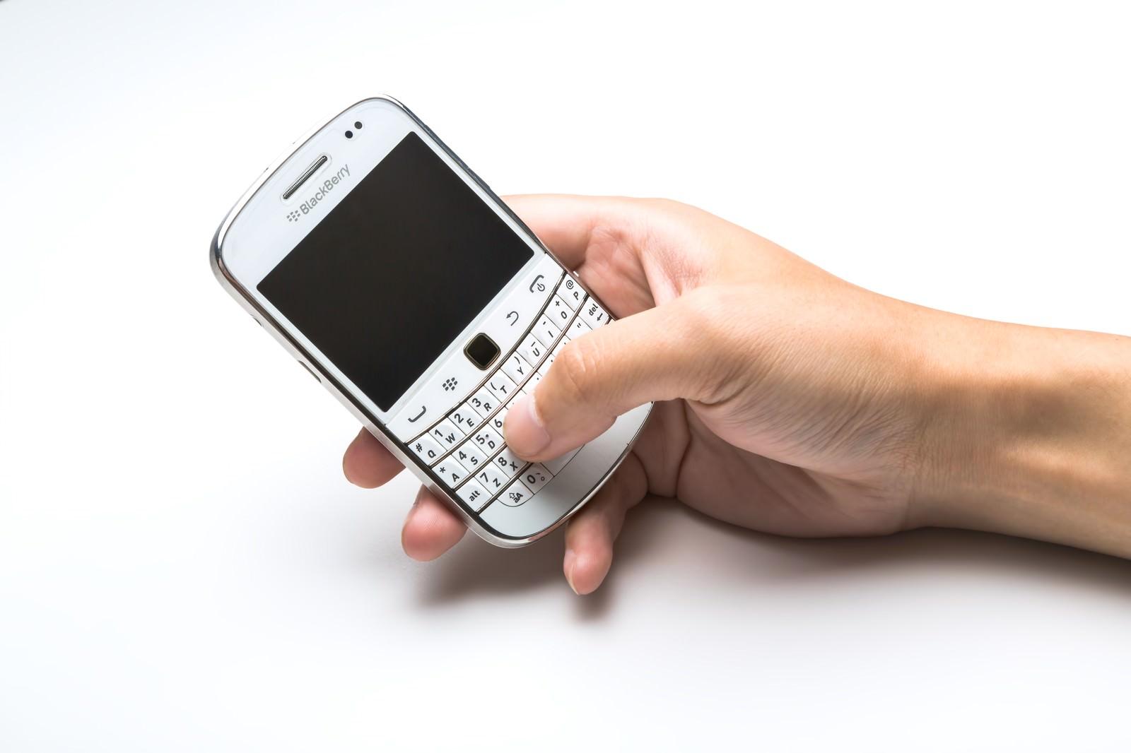 「BlackBerryを操作する手」の写真