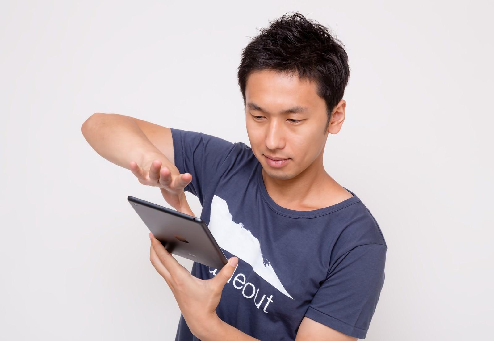 「iPad miniでスワイプする男性iPad miniでスワイプする男性」[モデル:大川竜弥]のフリー写真素材を拡大