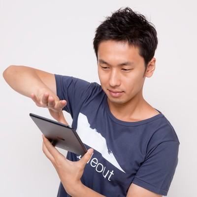 「iPad miniでスワイプする男性」の写真素材