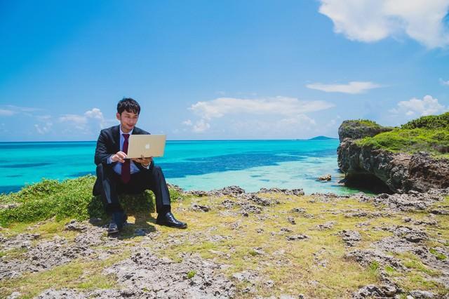 南国の海でも更新作業を怠らない意識の高いスーツ姿のブロガーの写真