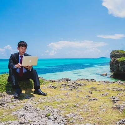「南国の海でも更新作業を怠らない意識の高いスーツ姿のブロガー」の写真素材